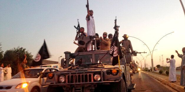 FILE - In this photo taken Monday, June 23, 2014, fighters from the Islamic State group parade in a commandeered Iraqi securi