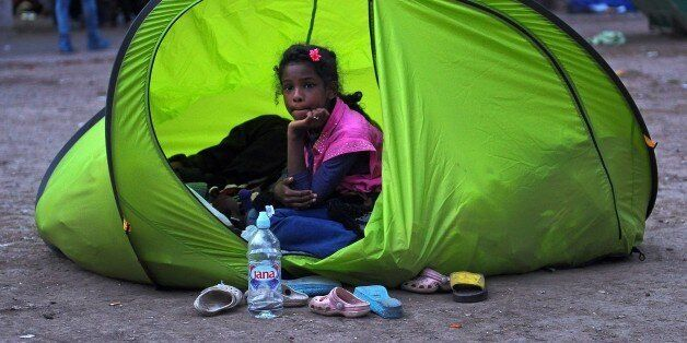 A young migrant sits in a tent in a park in Belgrade on September 9, 2015. The EU unveiled plans to take 160,000 refugees fro