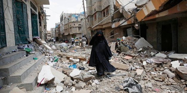 A woman walks amid the rubble of houses destroyed by a Saudi-led airstrike in Sanaa, Yemen, Monday, Sept. 21, 2015. Late Sund