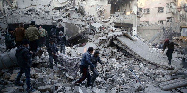 Syrians and civil defence workers evacuate victims from the rubble of a destroyed building following air strikes on the Easte