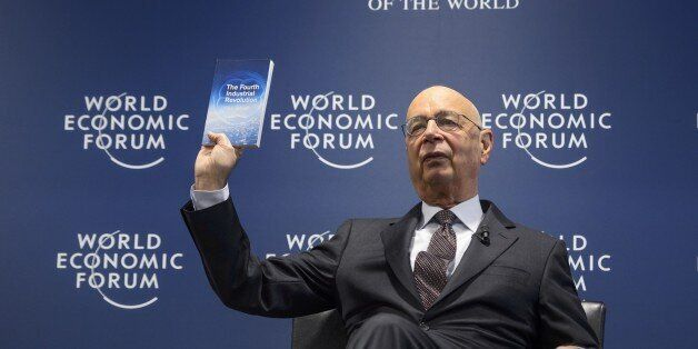 World Economic Forum (WEF) founder and executive chairman Klaus Schwab shows a book he wrote during a news conference on the