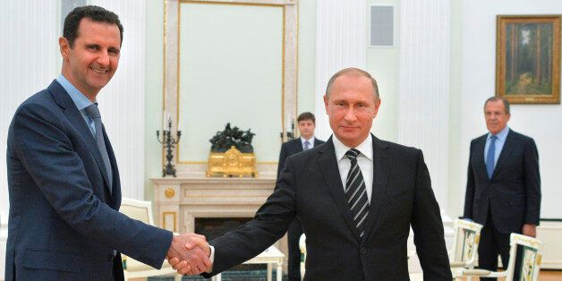 FILE - In this file photo taken on Tuesday, Oct. 20, 2015, Russian President Vladimir Putin, center, shakes hand with Syrian
