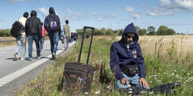 A migrant prays beside a freeway north of Rodby as a large group of migrants, mainly from Syria, walk on the highway towards