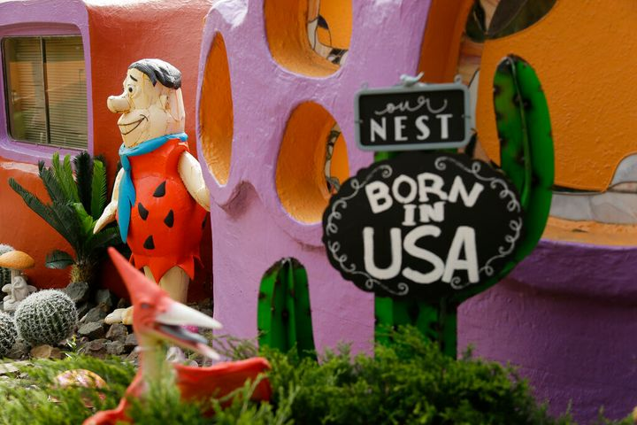 A statue of Fred Flintstone stands near the front entryway of the Flintstone House in Hillsborough, Calif. Technically, the owner of the fanciful Flintstones house in a posh San Francisco suburb settled a lawsuit with the town of Hillsborough. But the agreement will allow Fred and his friends to remain. (AP Photo/Eric Risberg, File)