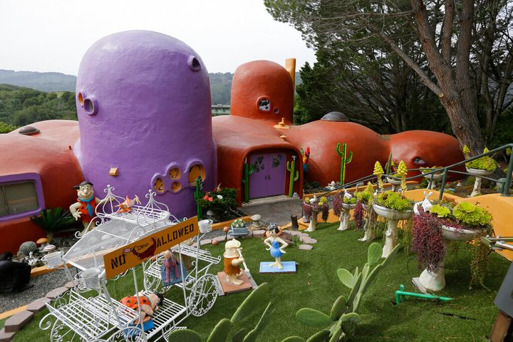 """The Flintstone House is seen before a news conference with the owner and the home's original architect in Hillsborough, Calif. The San Francisco Bay Area suburb of Hillsborough is suing the owner of the house, saying that she installed dangerous steps, dinosaurs and other Flintstone-era figurines without necessary permits. In a yabba dabba dispute that pitted property rights against government rules that played out in international media, retired publishing mogul Florence Fang defended her colorful, bulbous-shaped house and its elaborate homage to """"The Flintstones"""" family, featuring Stone Age sculptures inspired by the 1960s cartoon, along with aliens and other oddities. (AP Photo/Eric Risberg, File)"""