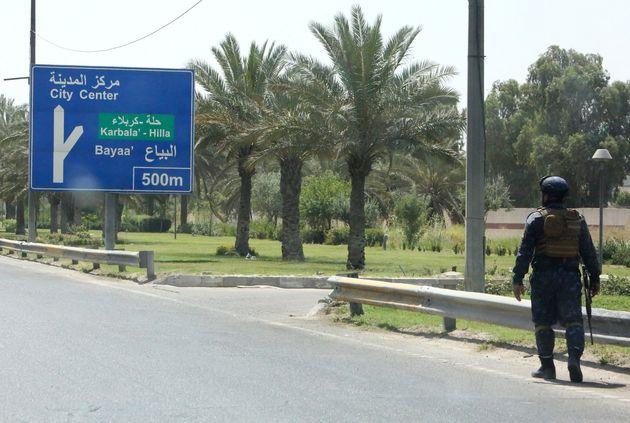 Un agente iraquí vigila los alrededores del aeropuerto internacional de Bagdad, atacado el mes...