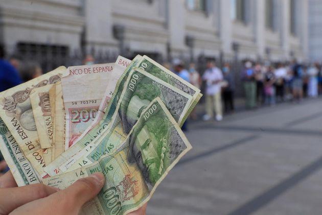 Una persona muestra varios billetes de las antiguas pesetas mientras espera cola a las puertas del Banco...