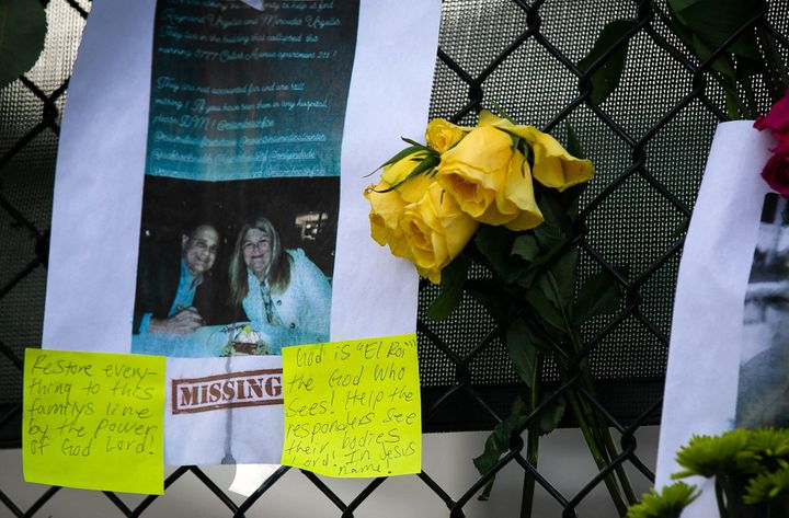 Photos of missing residents are posted at a makeshift memorial.