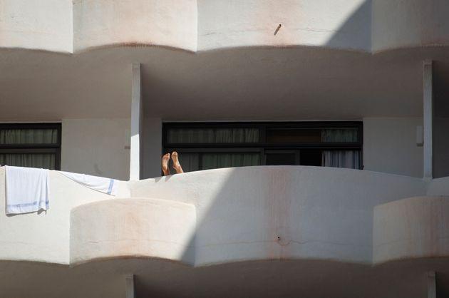 Un estudiante descansa con los pies en el balcón del 'hotel puente' en Mallorca, donde hacen cuarentena...