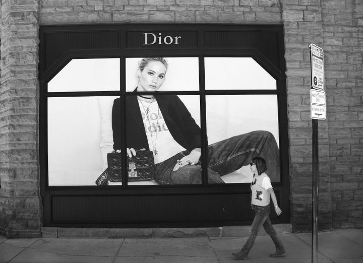 A tourist walks past a window display featuring a photograph of actress Jennifer Lawrence at a Dior store in Aspen, Colorado.