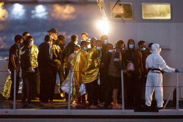Migrants queue onboard a Guardia di Finanza (Finance police) boat before disembarking on the Sicilian...