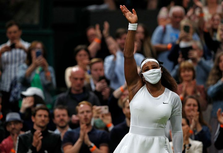 Serena Williams waves goodbye after withdrawing from the match at Wimbledon.