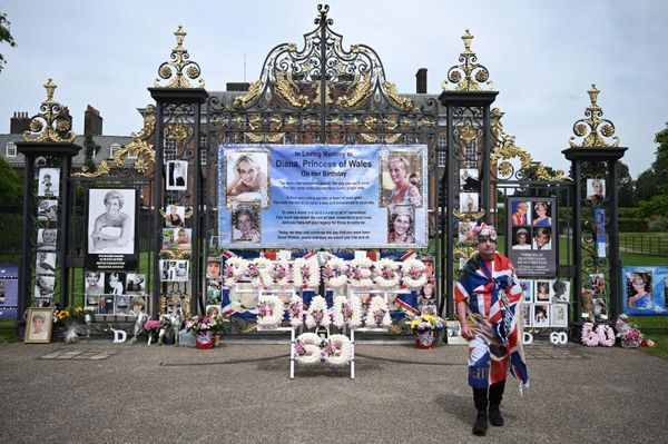 Royal fan John Loughrey poses by lettered wreaths and pictures attached to the gates of Kensington Palace to celebrate what w