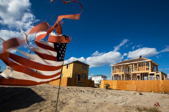 A tattered U.S. flag waves in the wind as construction workers build new homes in an area of Breezy Point in Queens, New York