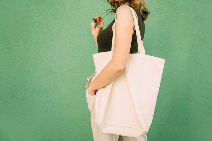 Beautiful blonde girl with eco bag over green background
