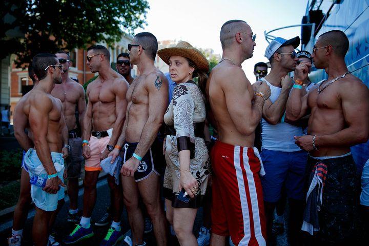Mujer pasando entre grupo de hombres gais en el desfile del Orgullo en 2013.