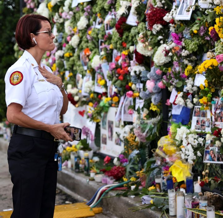 Miami-Dade Fire Rescue Chief Melanie C. Adams visits the makeshift memorial setup near the partially collapsed 12-story Champ