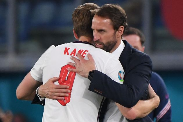 England's coach Gareth Southgate (R) greets England's forward Harry Kane after being substituted during...