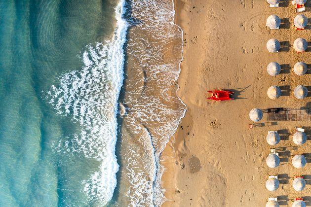 Aerial view of crashing waves on empty beach with white parasols, Vieste, Foggia province, Gargano, Apulia,