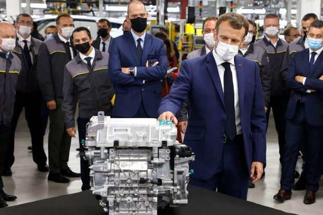 Le président Emmanuel Macron étudie un moteur lors d'une visite du site de la future usine du fabricant...