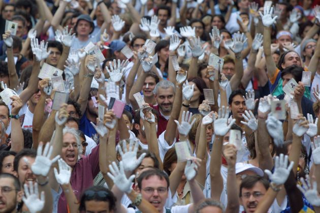 392106 08: Pro-immigration activists with white-stained hands take part in an anti-G8 demonstration July...