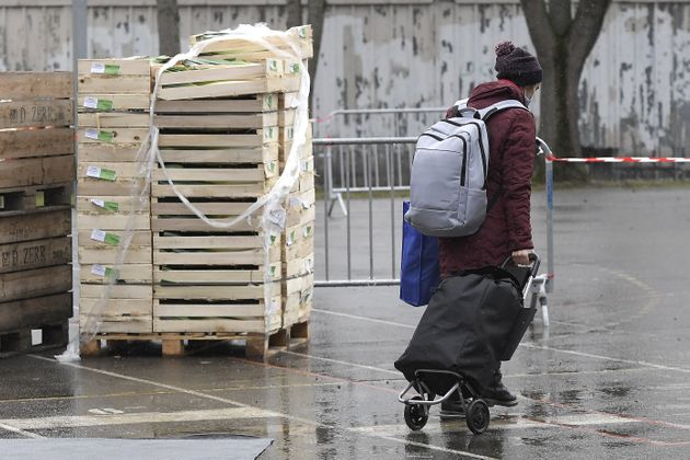 Un jeune homme porte des sacs après une distribution d'aide alimentaire par l'association caritative...