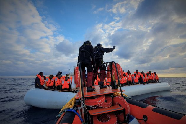 Mετανάστες με κόκκινα σωσίβια στη διάρκεια επιχείρησης διάσωσης από την οργάνωση SOS Mediterranee και...