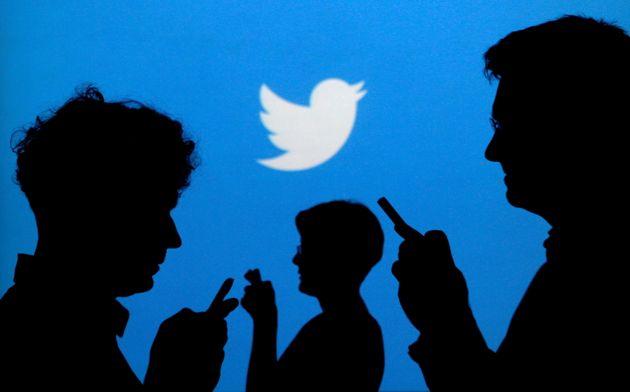 Des silhouettes devant un logo Twitter, photo prise le 27 septembre