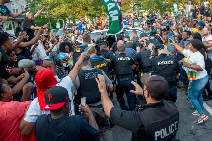 Police escort Edward Cagney Mathews through a crowd of people outside his Mount Laurel, New Jersey, home on Monday.
