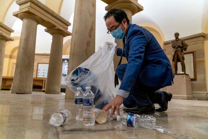 Rep. Andy Kim, D-N.J., cleans up debris and trash strewn across the floor in the early morning hours of Jan. 7, 2021, after p