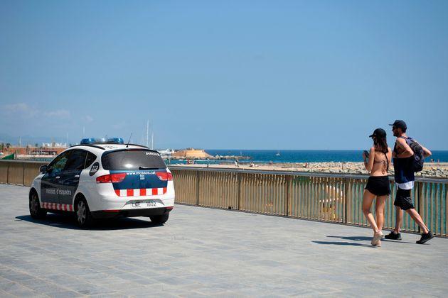 Imagen de archivo. Un coche de los Mossos pasa por delante de una playa en