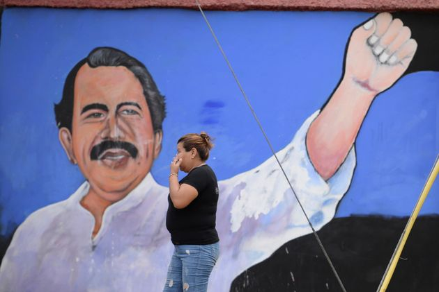 Una mujer camina frente a un mural del presidente de Nicaragua, Daniel