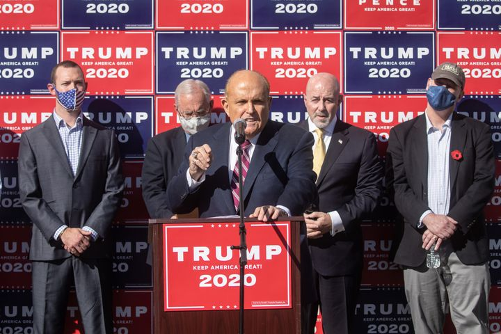 """<a href=""""https://www.huffpost.com/news/topic/rudy-giuliani"""">Rudy Giuliani,</a>&nbsp;center, was suspended from practicing law"""