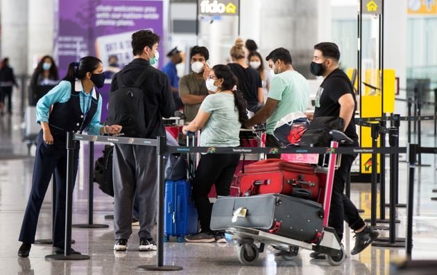 Travelers wearing face masks wait for shuttle buses at Toronto Pearson International Airport in Mississauga,...