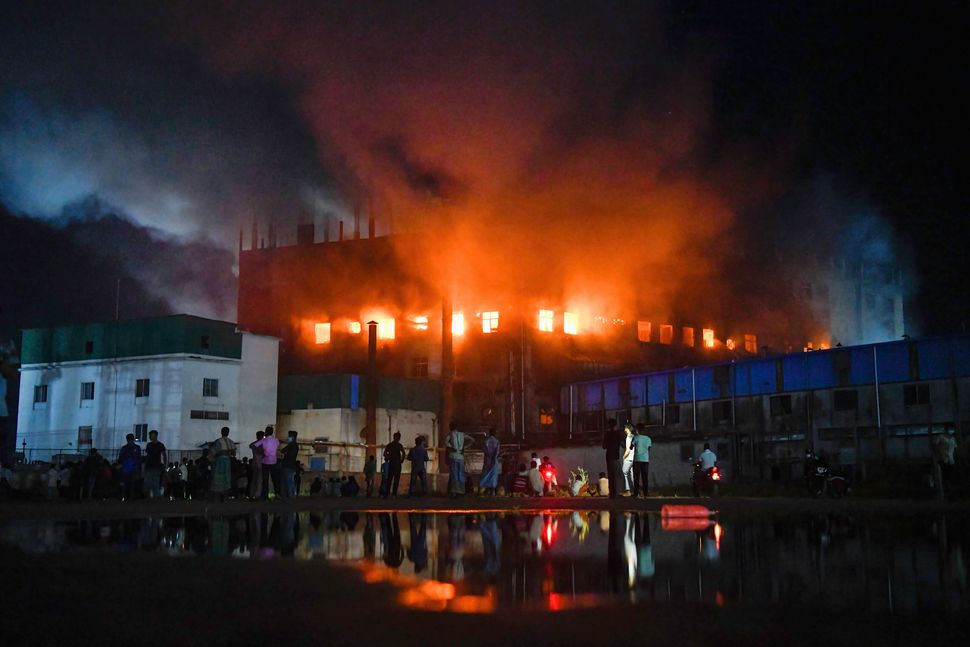 Firefighters try to extinguish fire inside the Hashem Foods Ltd factory on the outskirts of Dhaka.