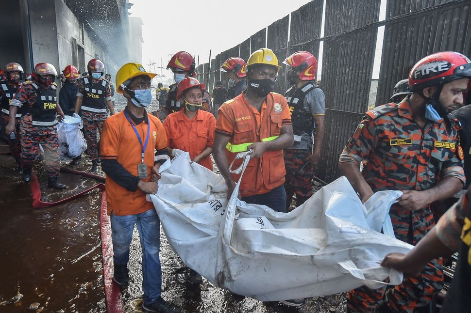 Rescue workers recover the bodies of the deceased who died in the blaze on Friday.