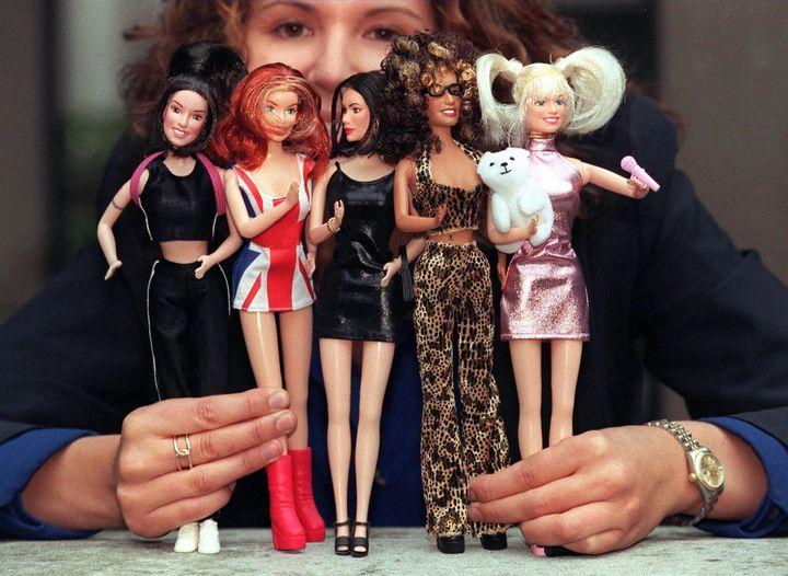 Niña sostiene las muñecas de las Spice Girls en 1997.