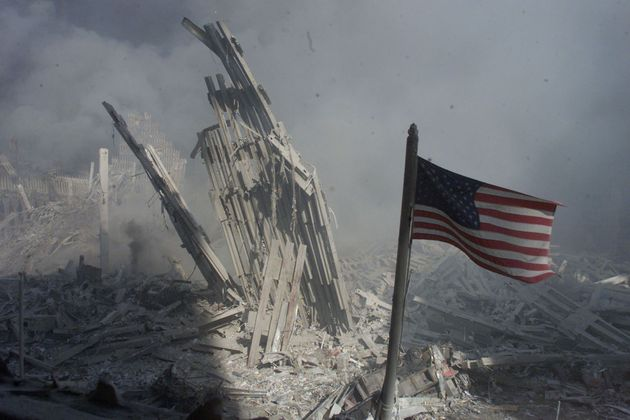 An American flag flies near the base of the destroyed World Trade Center in New York, in this file photo from September 11, 2001, taken after the collapse of the towers. This year's anniversary of the September 11 attacks in New York and Washington will echo the first one, with silence for the moments the planes struck and when the buildings fell, and the reading of 2,792 victims' names. REUTERS/Peter Morgan-Files HB