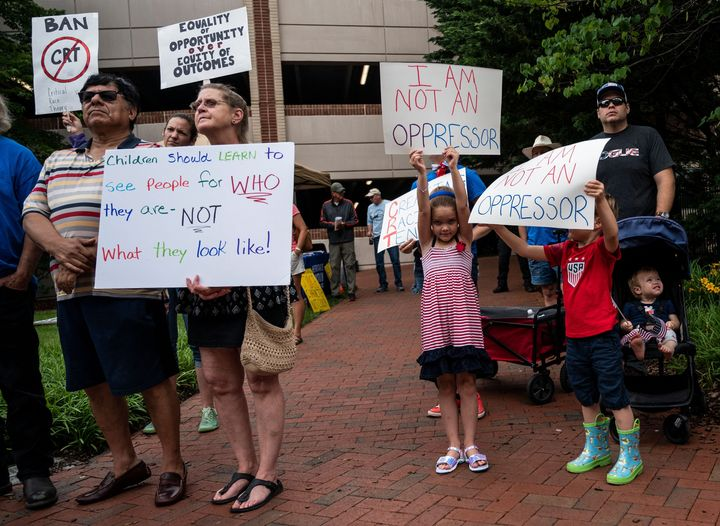 """People hold up signs during a rally against """"critical race theory"""" (CRT) being taught in schools at the Loudoun County Govern"""