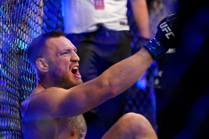 Conor McGregor yells as he sits on the mat after an injury during his lightweight mixed martial arts bout with Dustin Poirier