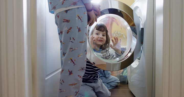 Young woman putting laundry in a washing machine while her kids help her