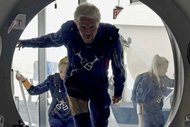 Richard Branson and Virgin Galactic crew members enter the company's passenger rocket plane, the VSS...