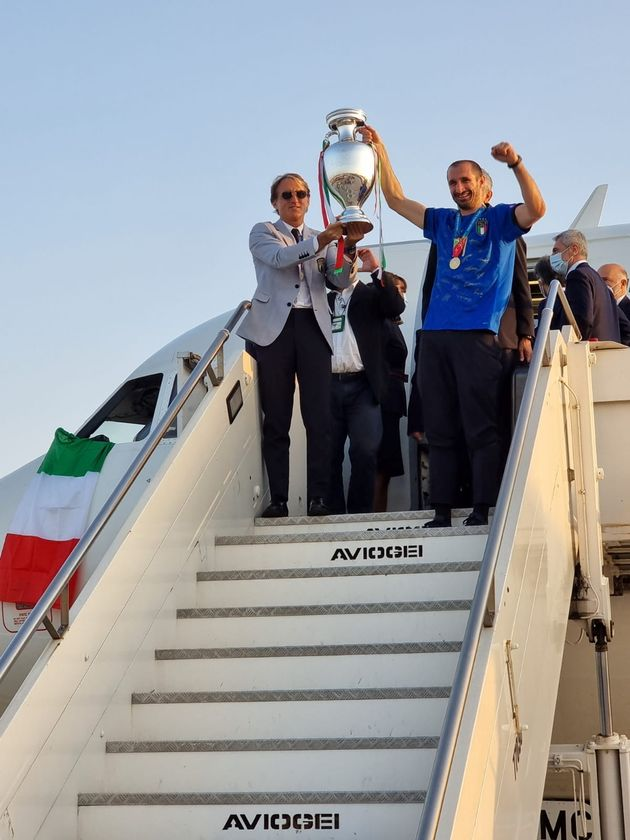 Italy coach Roberto Mancini and captain Giorgio Chiellini walk down steps of a plane holding the Euro 2020 cup at Fiumicino airport near Rome, Italy, July 12, 2021. Aeroporti di Roma/Handout via REUTERS THIS IMAGE HAS BEEN SUPPLIED BY A THIRD PARTY. NO RESALES. NO ARCHIVES. MANDATORY CREDIT