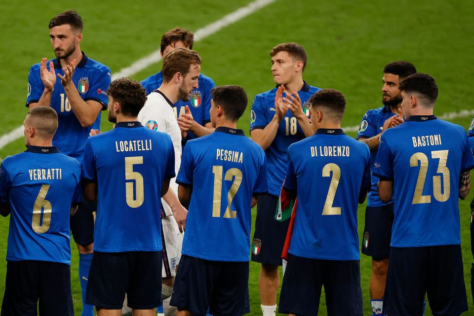 TOPSHOT - Italy players applaud as England's forward Harry Kane (C) walks between them after italy won...