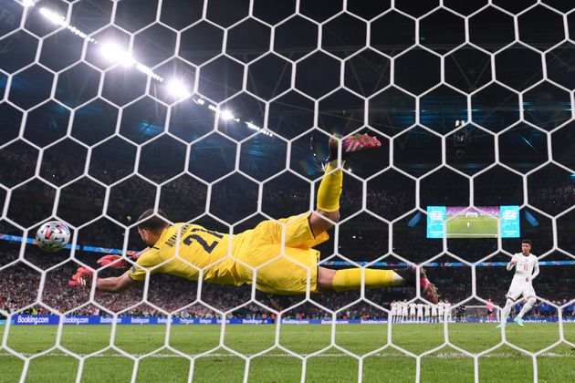 LONDON, ENGLAND - JULY 11: Jadon Sancho of England has their team's fourth penalty saved by Gianluigi Donnarumma of Italy in a penalty shoot out during the UEFA Euro 2020 Championship Final between Italy and England at Wembley Stadium on July 11, 2021 in London, England. (Photo by Laurence Griffiths/Getty Images)