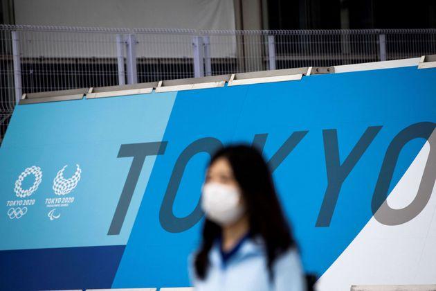 Une femme masquée devant le centre de presse des Jeux olympiques de Tokyo le 9 juillet 2021 (photo