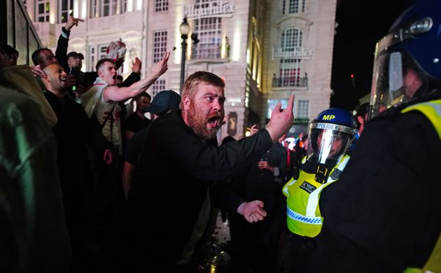 Editors: please note gestures. Police and England fans in London's Piccadilly Circus after Italy won...
