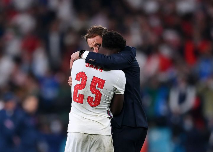 Bukayo Saka of England is consoled by head coach Gareth Southgate after his penalty miss during the UEFA Euro 2020 Championsh