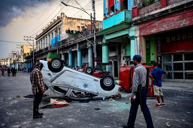 TOPSHOT - Police cars are seen overturned in the street in the framework of a demonstration against Cuban President Miguel Diaz-Canel in Havana, on July 11, 2021. - Thousands of Cubans took part in rare protests Sunday against the communist government, marching through a town chanting