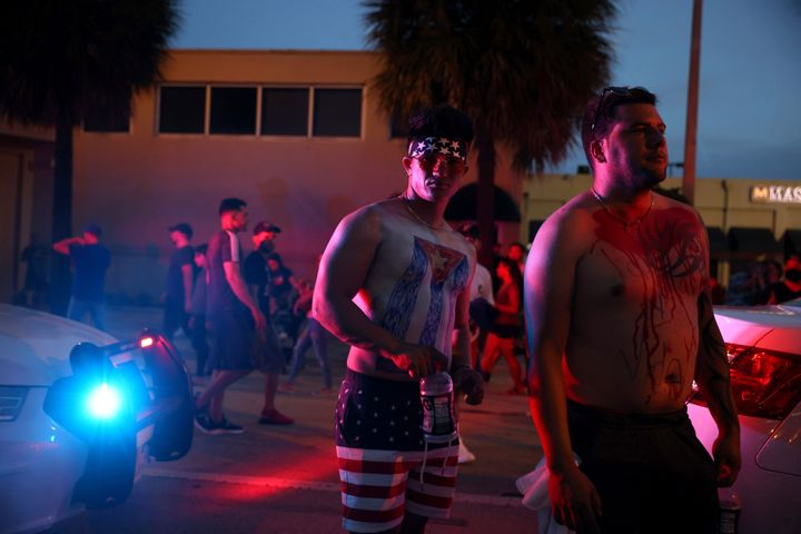 Two people with the Cuban flag painted on themselves demonstrate in the street near Versailles, a Cuban restaurant in Miami's